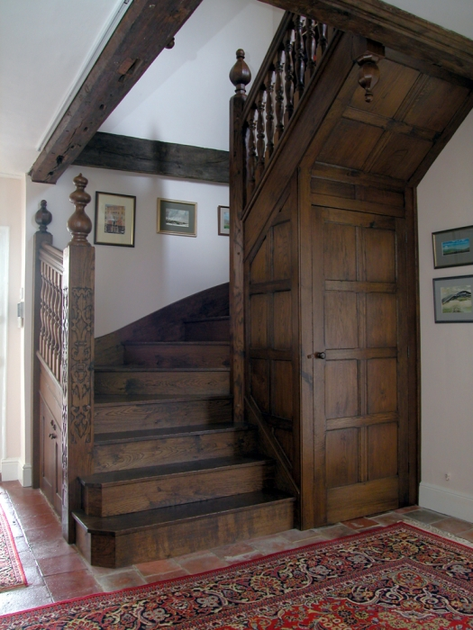 Oak Staircase with Hand Carved Newels, Turned Spindles and Cupboard under,the octagonal centre post gives maximum clearance on Stairs