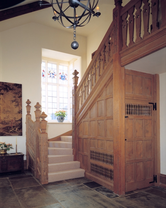 Oak Staircase with Hand Carved Newel Post and Fretted Splats, Turned Spindles leave air space for heating in Understairs Cupboard. The heavy sections and large Finials are balanced by the light colour