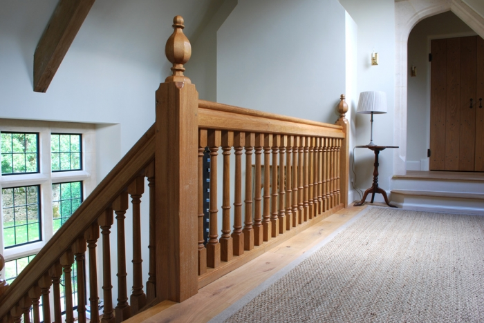 Light Oak Gallery with Heavy Sectioned Newel Posts and Handrail, and Faceted Newel Caps
