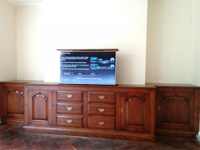 Fitted Oak TV and Media Cabinet, the TV rises and lowers with a remote controlled lift system. The drawer fronts are false and lift out to give access to the power unit and wiring. The left centre door opens and slides back into the unit to leave set top boxes etc unobstructed whilst in use.
