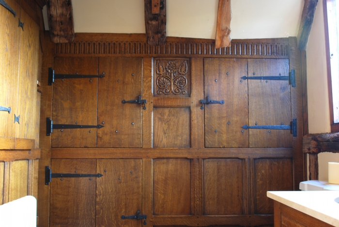 Fitted Oak Cupboard with Hand Carving and Forged Ironmongery the Carved Rail has been expertly Scribed to fit around the Beams and Ceiling shape