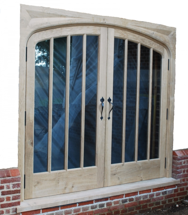 A pair of Glazed Oak Doors with Heavy Sectioned Hand Carved Frame
