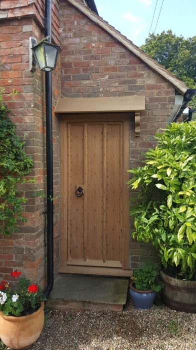 Solid Oak Planked Exterior Door with Canopy and Hand Carved Bracket