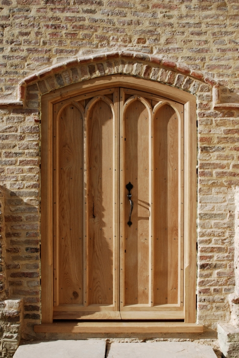 A pair of Arched Solid Oak Exterior Doors with Shaped Cover Mouldings and a Heavy Sectioned Moulded Frame